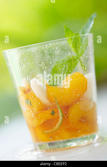 Yellow and white peach salad with fresh mint - Stock Image
