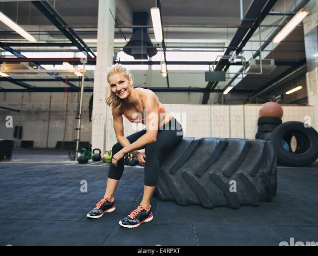 Woman sitting on tire and smiling at camera at gym. Crossfit female athlete taking rest after working out. - Stock Image