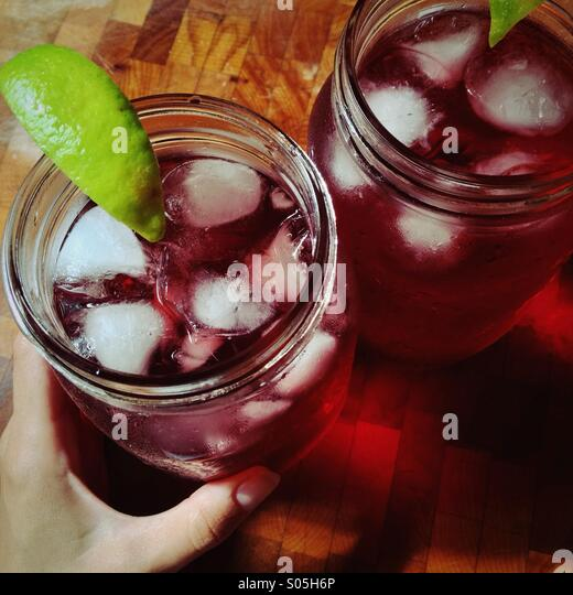 Two large jars of red iced hibiscus tea drinks with lime wedges on wood chopping block with hand in frame - Stock Image