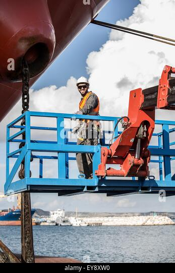 Portrait of worker on viewing platform inspecting oil tanker - Stock Image