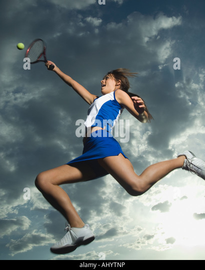 Low angle view of tennis player jumping - Stock Image