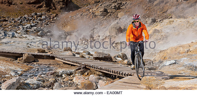 Young male cyclist riding hybrid bike at geothermal site, Krysuvik, Reykjanes, Iceland - Stock Image