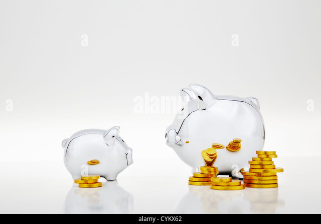 Stacks of gold coins by piggy banks - Stock Image