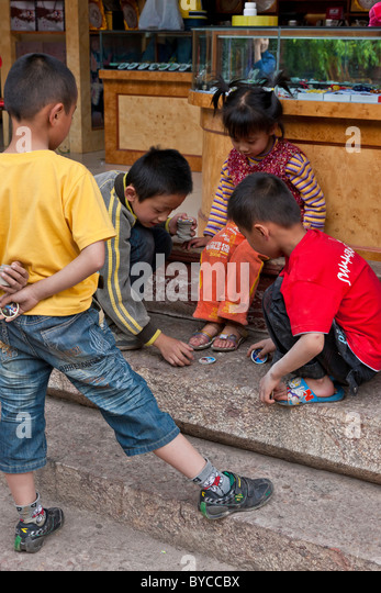 Young children playing game in the Old Market Square, Lijiang, Yunnan Province, China. JMH4750 - Stock Image
