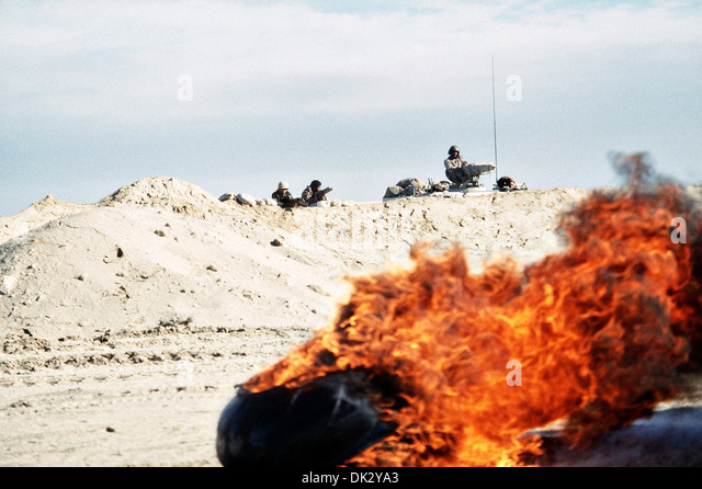 Armored units wait along a sand berm as destroyed vehicles burn during Operation Desert Storm February 28, 1991 - Stock Image