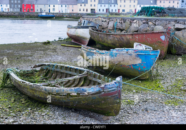 Old boats near the Claddagh with the Long Walk and Old Quays to the rear, Galway city, Ireland. - Stock Image