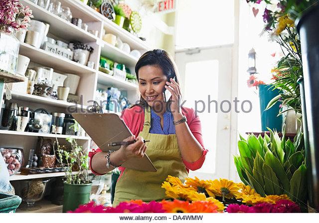 Female florist taking order on mobile phone in flower shop - Stock Image