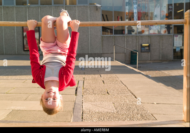 young girl 9 year old girl in red jacket playing outdoors hanging upside down on wooden bar - Stock Image