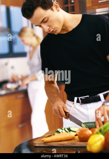 Man slicing vegetables in kitchen, mid-section - Stock Image