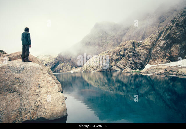 Man Traveler standing alone on stone cliff lake and misty mountains on background Travel Lifestyle concept outdoor - Stock Image