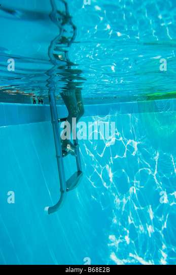 Legs on step ladder in swimming pool - Stock Image