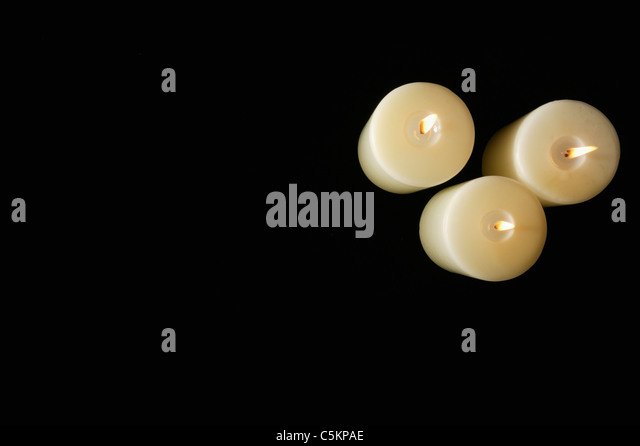 Three thick white candles seen from above on black background - Stock Image