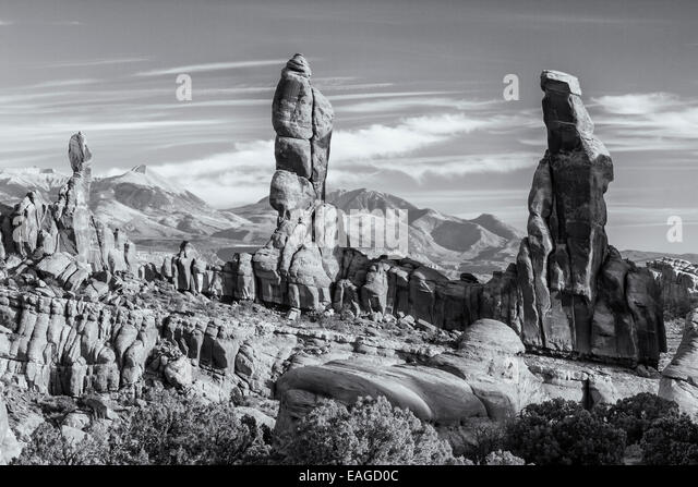 Black and white photo of four 'Marching Men' sandstone pillars in front of the La Sal Mountains in the Klondike - Stock Image