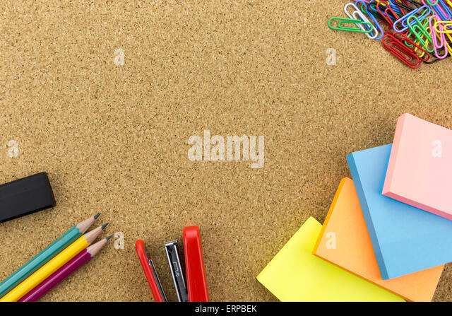 wallpaper stationary on cork board with many office supplies tools - Stock Image