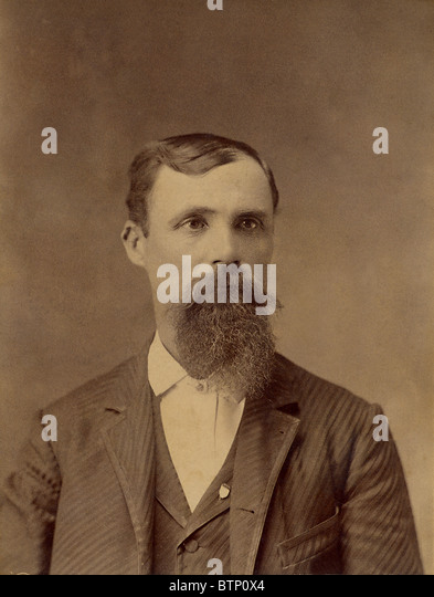 1800's vintage antique portrait photo of a gentleman wearing a suit with a long beard. The photograph is yellowed - Stock Image