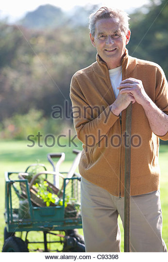 Portrait of smiling senior man with gardening tools - Stock-Bilder