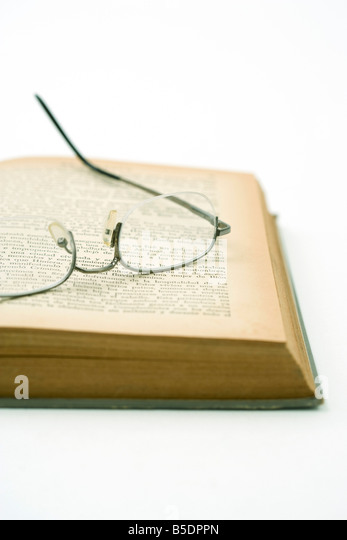 Pair of glasses resting on yellowed page of open book - Stock Image
