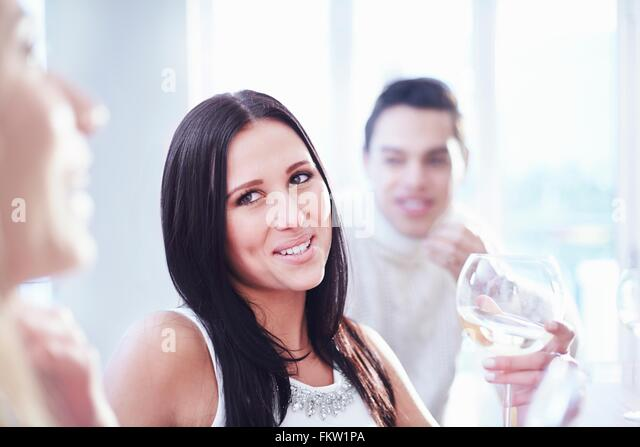 Cropped view   three young adult friends chatting and drinking wine in kitchen - Stock Image