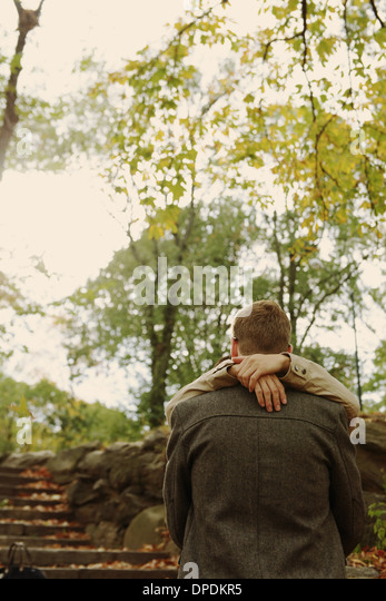 Gay couple hugging by steps - Stock Image