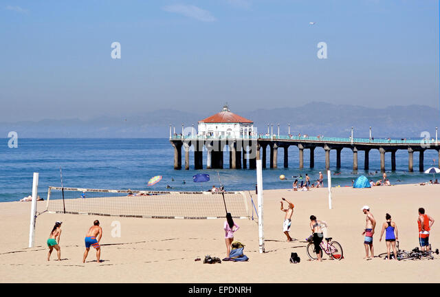 men and women play volleyball on Manhattan Beach California with the pier in the background - Stock Image