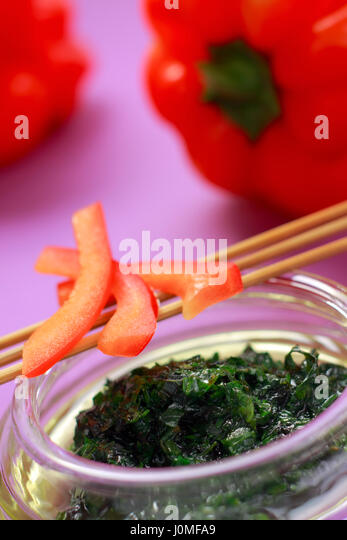 Herbal green dressing in glass bowl and red paprika parts with unfocused background - Stock Image