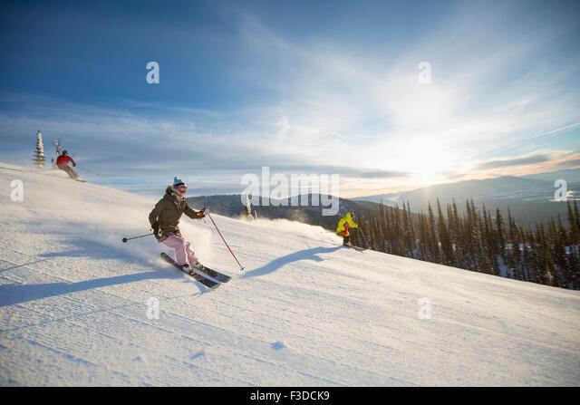Three people on ski slope at sunlight - Stock Image