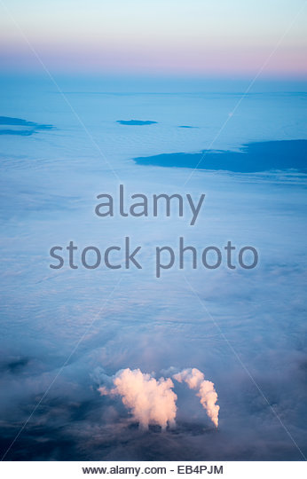 Aerial of pink sunrise light illuminating smoke rising from smokestacks over a background of ground fog at a major - Stock-Bilder