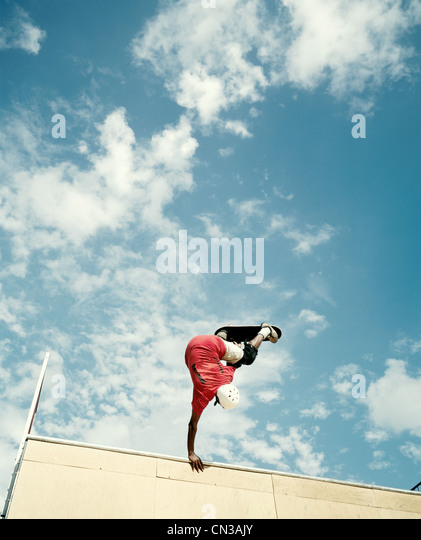 Young man skateboarding, low angle view - Stock Image