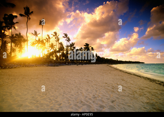 Palm trees are silhouetted by the setting sun in a colorful sky a beach Punta Cana Domincan Republic - Stock Image