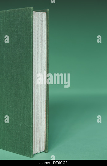 A hard cover book with a green cover, and white paper page edges, upright on a green background. - Stock Image