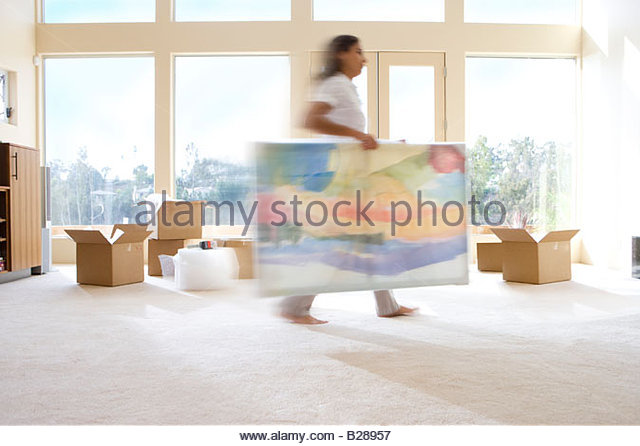 Woman carrying artwork in new home - Stock Image