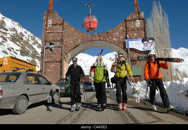 Four men carrying skis after a days skiing at Dizin in the Alborz mountains of Iran - Stock Image