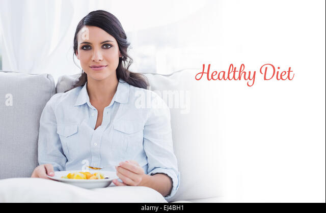 Healthy diet against pretty woman sitting on the couch eating fruit salad - Stock Image