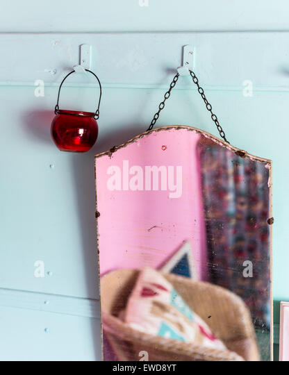 Vintage mirror and candle holder hanging from coat hook rack on sky blue coloured wall - Stock Image