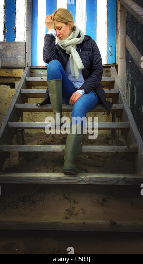 sad young woman sitting on beach cabin stairs - Stock Image