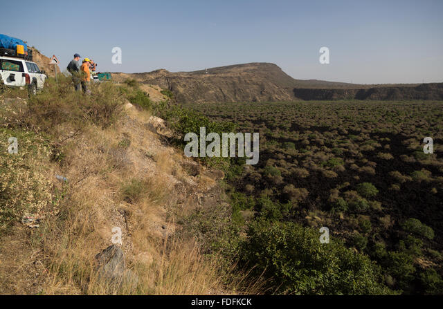 Travellers look out over a recent lava flow which has been colonised by low bushes in eastern Ethiopia - Stock Image