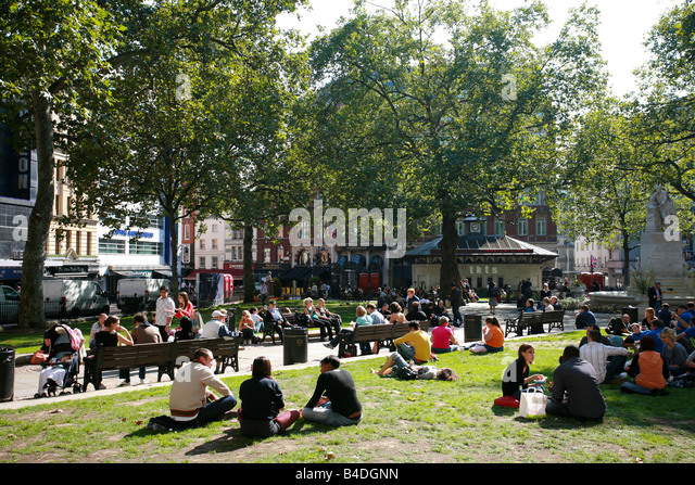 Tourists and students enjoy sunshine relaxing on grass in Leicester Square London West End theatre entertainment - Stock Image