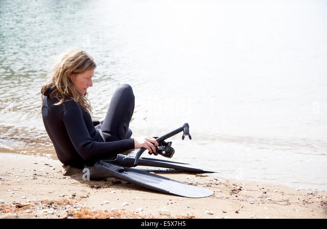 Mid adult female scuba diver preparing to dive on beach - Stock Image