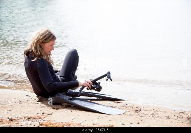 Mid adult female scuba diver preparing to dive on beach - Stock-Bilder