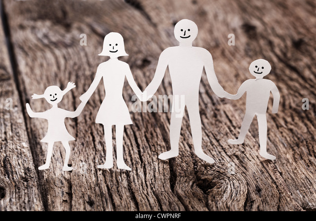 Cardboard figures of the family on a wooden table. The symbol of unity and happiness. - Stock Image
