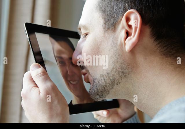Mid adult man kissing screen of digital tablet - Stock Image