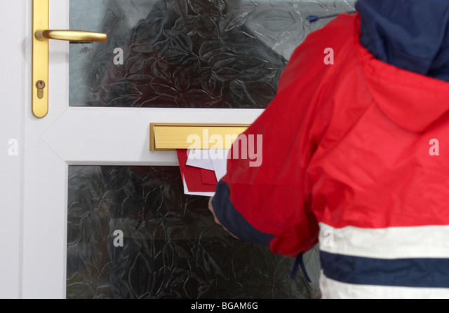 postman posting letters and cards through the letterbox of a house in the uk - Stock Image