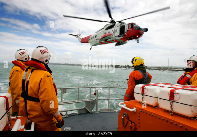 RNLI Yarmouth lifeboat exercise with Air sea Rescue Helecopter India Juliet Isle of Wight England UK - Stock Image