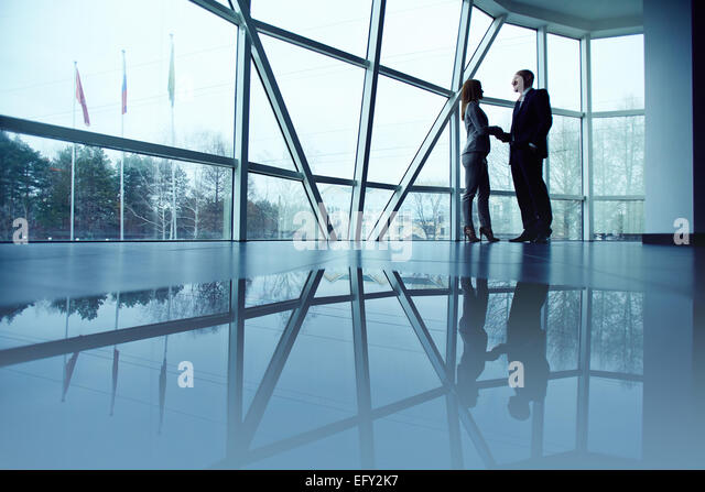 Outlines of co-workers handshaking in office - Stock Image
