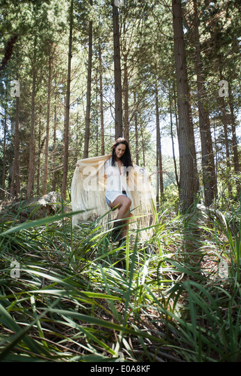Young woman walking through forest - Stock Image