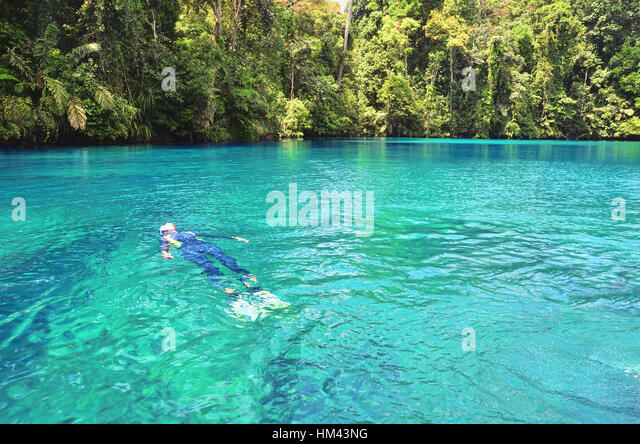 Swimmer floating on the surface of Labuan Cermin Lake - Stock Image