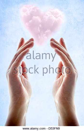 Hands with pink heart shaped cloud floating above them - Stock-Bilder