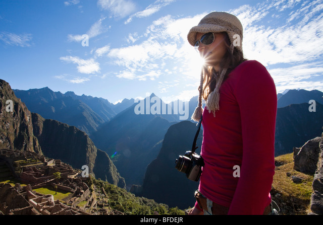 Young girl stands with camera around her neck overlooking a steep valley, the rising sun, and the ruins of a lost - Stock Image