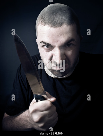 Ugly criminal with stockings over face and knife in his hand - Stock Image