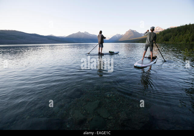 A man and woman stand up paddle boards (SUP) on Lake McDonald in Glacier National Park. - Stock Image